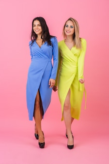 파란색과 노란색 색상의 세련된 화려한 드레스, 여름 패션 트렌드에 분홍색 벽에 포즈 두 세련된 섹시 웃는 매력적인 금발 머리와 갈색 머리 여자