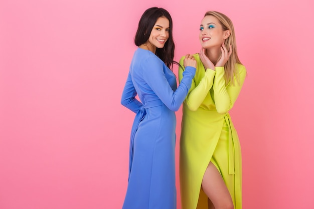 Two stylish sexy smiling attractive women posing on pink wall in stylish colorful dresses of blue and yellow color, summer fashion trend