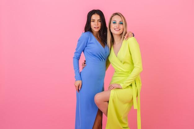 파란색과 노란색 색상의 세련된 화려한 드레스, 봄 패션 트렌드에 분홍색 벽에 포즈 두 세련된 웃는 매력적인 여자 친구