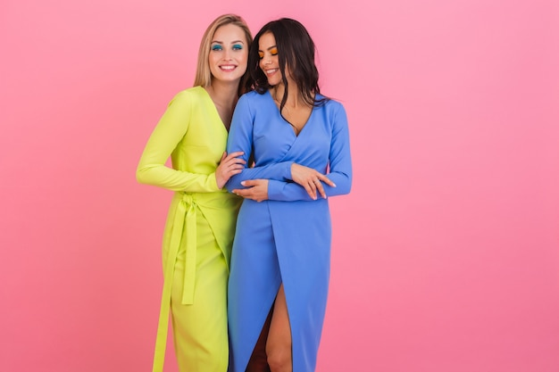 Two stylish smiling attractive women friends posing on pink wall in stylish colorful dresses of blue and yellow color, spring fashion trend