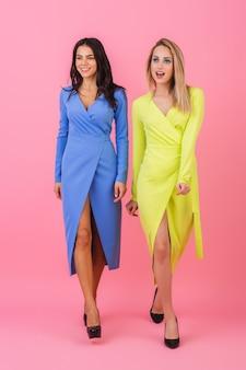 青と黄色のスタイリッシュなカラフルなドレス、春のファッショントレンド、人差し指でピンクの壁にフルハイトで一緒に歩いている2人のスタイリッシュな笑顔の魅力的な女性