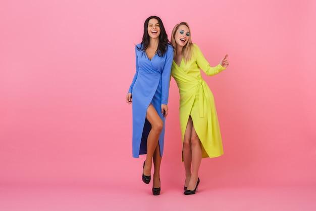 분홍색 벽, 파란색과 노란색 색상 의류, 여름 패션 트렌드에 전체 높이를 포즈를 취하는 재미 화려한 드레스를 입고 두 세련된 웃는 매력적인 여성