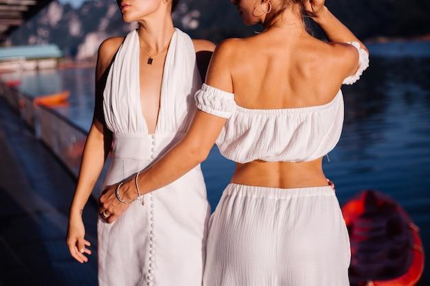 Due donne alla moda in abiti estivi bianchi in posa vicino all'acqua