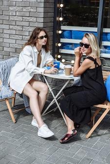 두 명의 세련된 여성이 레스토랑의 테이블에 앉아 있다
