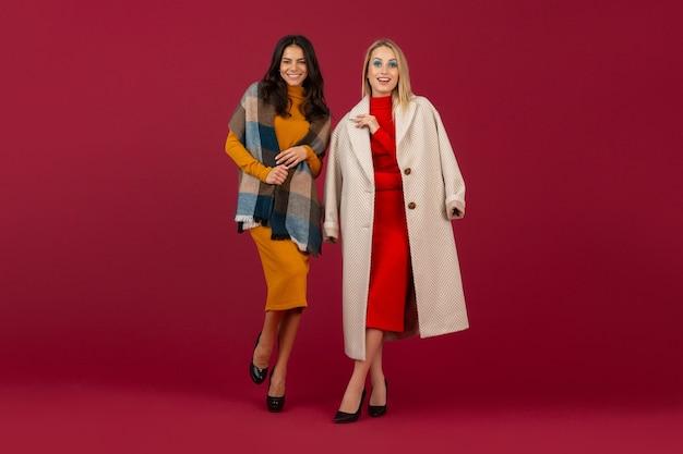 Due donne alla moda in abito da moda autunno inverno e cappotto in posa isolato sulla parete rossa