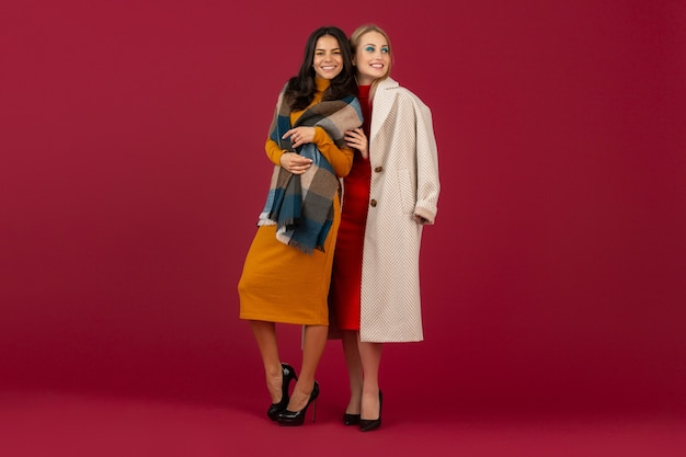 Two stylish women in autumn winter fashion dress and coat posing isolated  on red wall