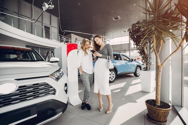 Two stylish women in a car salon