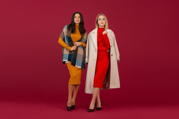 赤い壁に分離された秋冬のファッションドレスとコートのポーズで2人のスタイリッシュな女性