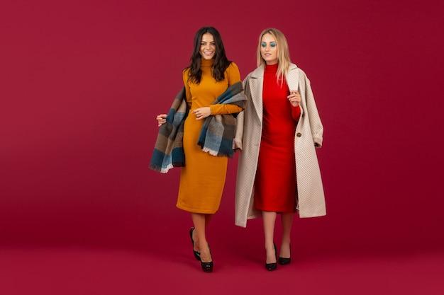 가을 겨울 패션 드레스와 코트에 두 세련된 여성이 붉은 벽에 고립 된 포즈