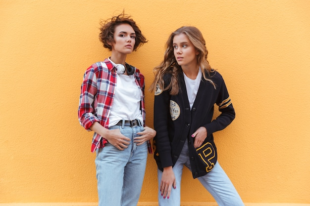 Two stylish young teenage girls posing while standing