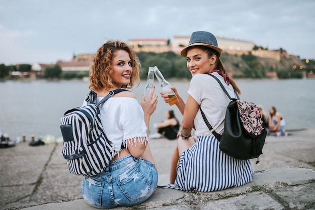 Two stylish young woman cheering while sitting near the river.
