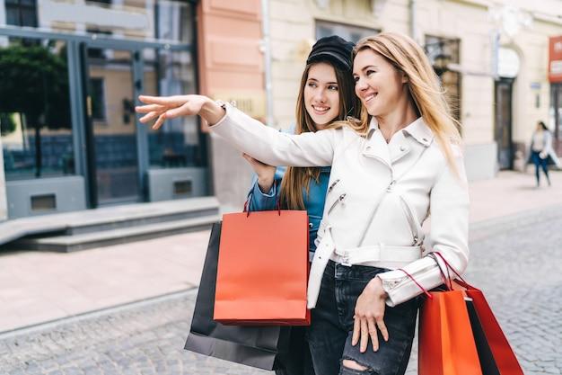 スタイリッシュな服を着た2人の女性がショーウィンドウで割引を見ました