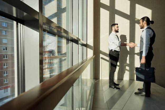 午前中にオフィスセンターの大きな窓のそばに立っている間、お互いに握手する2つの成功したビジネスパートナー