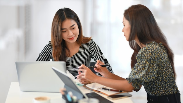 Two of successful businesswomen talking and brainstorming at workplace laptop and tablet on desk