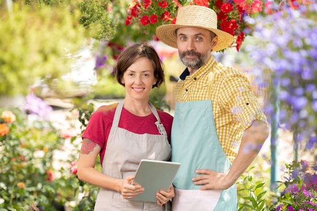 Two successful farmers in workwear while standing among blooming flowers in greenhouse