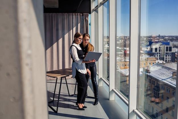 Две успешные женщины-архитекторы обсуждают совместный проект, стоя у окна с ноутбуком. молодые женщины-экономисты, одетые в формальную одежду, разговаривают во время перерыва в работе