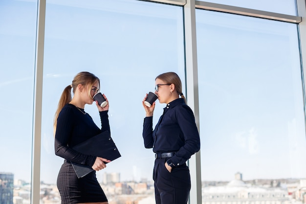 Two successful female managers talking about a joint project while standing by the window in the office. young women economists, dressed in formal attire, talk during their breaks and drink coffee.