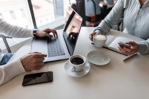 커피 한 잔을위한 창의적인 프로젝트를 진행하는 카페에 앉아있는 두 명의 성공적인 프리랜서