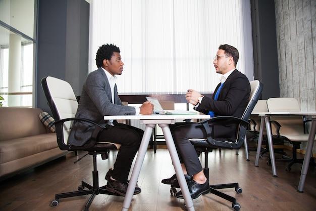 オフィスで成功した2人の男性起業家が一緒に働く