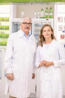 Два успешных профессионала в белых халатах стоят между большим дисплеем с лекарствами и прилавком в современной аптеке.