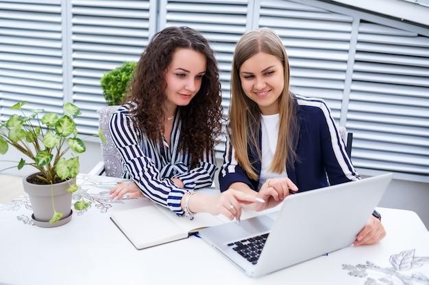 두 명의 성공적인 젊은 여성 매니저가 새로운 개발 프로젝트에서 노트북과 노트북을 들고 테이블에 앉아 있고, 여학생들은 컴퓨터 작업에 대한 보고서를 작성합니다.