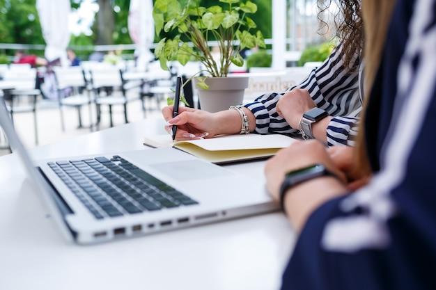 Две успешные молодые бизнес-леди-менеджеры сидят за столом с ноутбуком и блокнотом, работая над новым проектом развития, студентки пишут отчет о работе своего компьютера