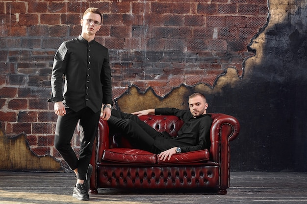 Два успешных молодых бизнесмена, улыбаясь, сидя на диване. современный молодой бизнес. скопируйте пространство.