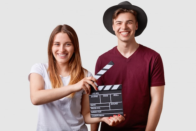 Two successful young female and male famous producers or directors hold film clapper, participate in shooting film, have joyful expressions, pose on white. film making concept.