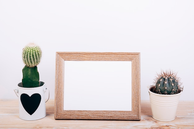 Two succulent plants on sides of empty photo frame on wooden desk