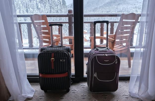 호텔 아파트의 탁 트인 창문 앞에 두 개의 여행 가방이 서 있으며 눈 덮인 산의 멋진 전망을 감상 할 수 있습니다.