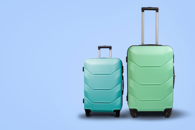 Two suitcases on wheels on a blue background. concept of travel, a vacation trip, a visit to relatives. pink and green color