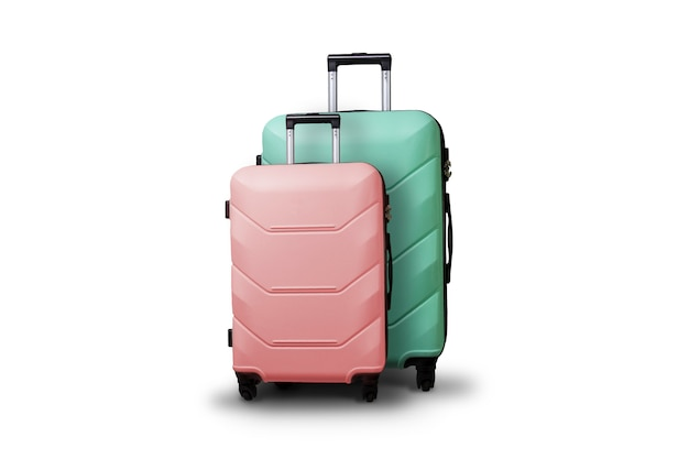 Two suitcases on wheels on a white isolated background. concept of travel, a vacation trip, a visit to relatives. pink and green color