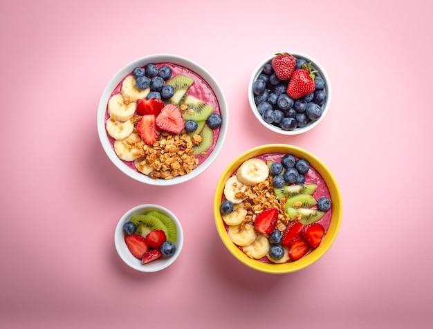 파스텔 핑크 배경에 딸기, 바나나, 블루베리, 키위 과일, 그래놀라를 넣은 여름 아사이 스무디 그릇 2개. 과일과 시리얼이 포함된 조식 그릇, 클로즈업, 위쪽 전망, 건강식