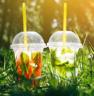 緑の芝生の屋外に立っている2つの夏のカクテル。冷たいノンアルコール飲料に氷を入れて持ち帰ります。モヒートとストロベリーレモネード、ライム、ソーダ水、ミント。鮮度と休日。