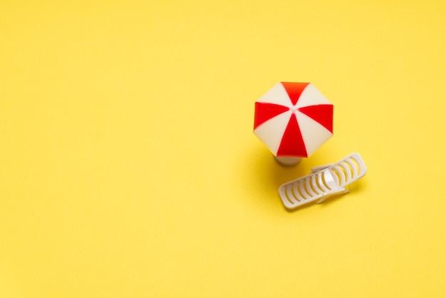 Два шезлонга и красный зонт на желтом фоне. скопируйте пространство.