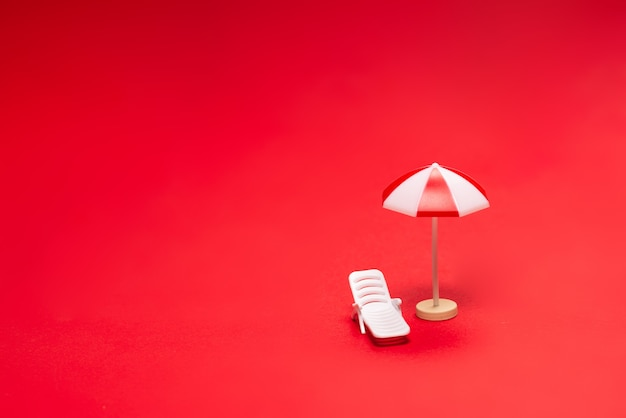 Два шезлонга и красные зонтики на красном фоне. скопируйте пространство.