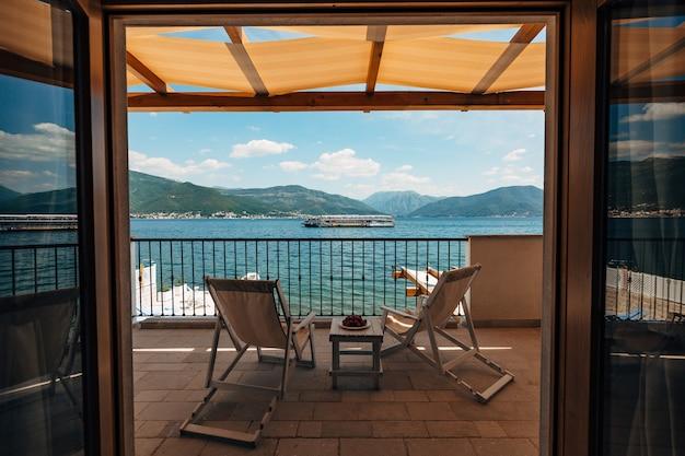 바다와 지나가는 관광 보트가 내려다 보이는 호텔 객실 발코니에있는 일광욕 용 라운 저 2 개