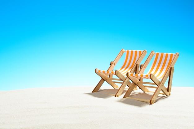 복사 공간이있는 모래 해변과 하늘에 두 개의 일광욕 의자