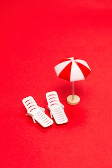 Two sun loungers and red umbrellas on a red background. copy space.