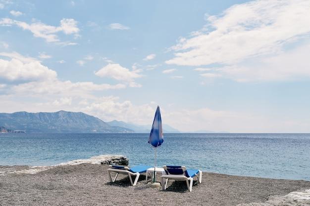 테이블이 있는 2개의 일광욕용 라운저가 바다 해변에 서 있습니다.