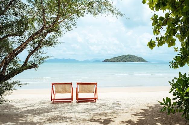 Two sunbeds on a beautiful sandy beach Premium Photo