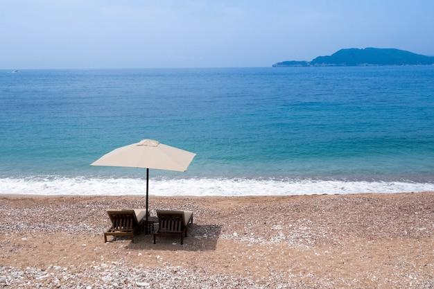Два шезлонга под зонтиком на пустом песчаном пляже