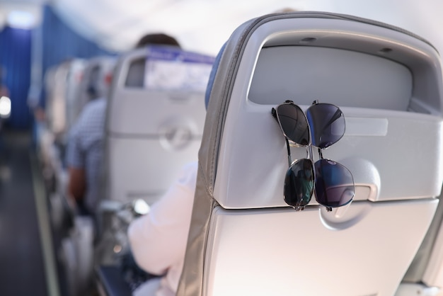 Two sunglasses hanging on back of passenger seat on airplane closeup