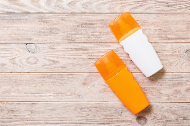 Two sunscreen bottles on a bright wooden background, top view with copy space.