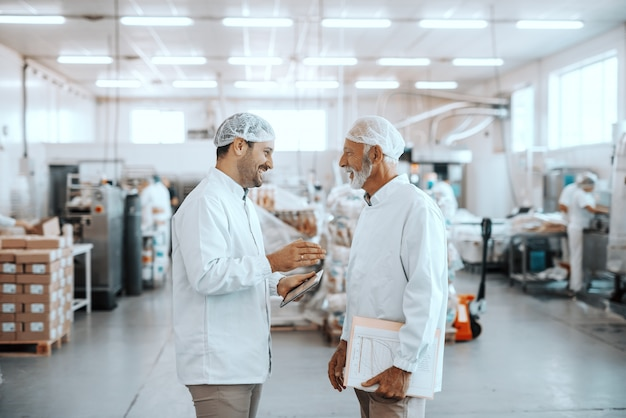 Two supervisors talking about quality of food. younger one holding tablet while older one holding folder with charts. both are dressed in sterile uniforms and having hairnets. food plant interior.