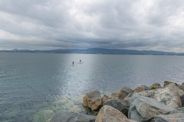 Two surfers are swimming on a surfboard in the waters of dublin bay.