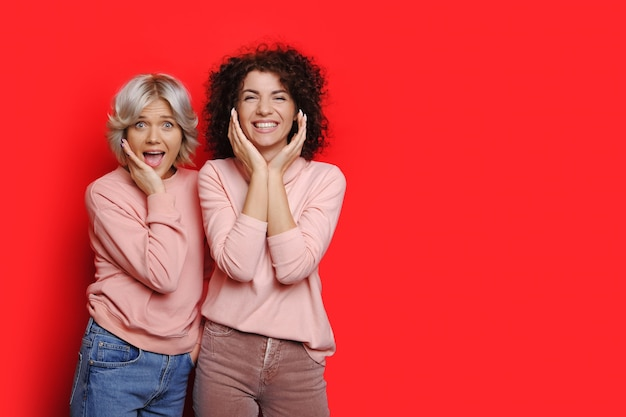 Two surprised caucasian women in pink sweaters and curly hair are posing on a red wall with free space