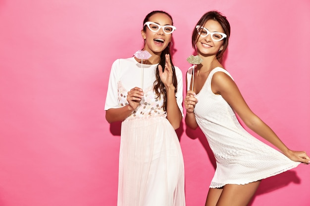 Two surprised funny women in paper glasses and big lips on stick. smart and beauty concept. joyful young models ready for party. women isolated on pink wall. positive female
