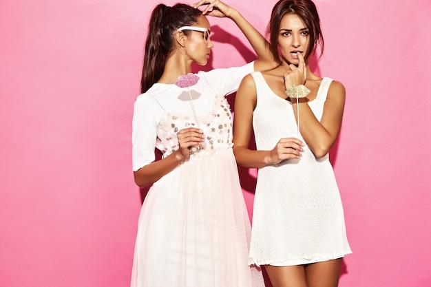 Due donne divertenti sorprese in bicchieri di carta e grandi labbra sul bastone. concetto intelligente e di bellezza. giovani modelle allegre pronte per la festa. donne isolate sulla parete rosa. femmina positiva