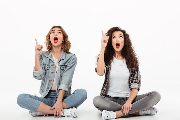 Две удивленные девушки сидят на полу вместе, указывая и глядя с открытыми ртами на белую стену